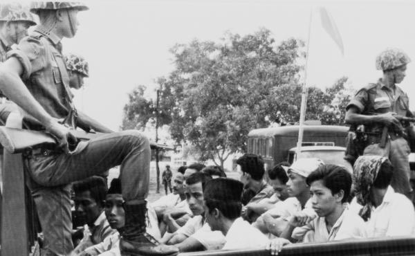 Indonesian soldiers stand guard over members of the youth wing of the Indonesian Communist Party, who were packed into a truck to be taken to a Jakarta prison in October 1965. Over the next few months, the government's military leadership carried out the