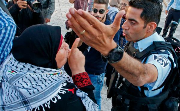 A Palestinian woman argues with a member of the Israeli security forces as they disperse a demonstration outside the Damascus Gate in the old city of Jerusalem on Tuesday.