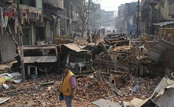 A municipal worker stands next to rubble on a street vandalized in New Delhi last month. Communal violence in India's capital killed more than 50 and injured more than 200 as President Trump was visiting the country. The violent clashes between Hindu and