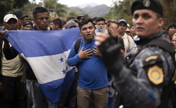 Honduran migrants walking in a group stop before Guatemalan police in January near Agua Caliente, Guatemala. The Democratic staff of the Senate Foreign Relations Committee says U.S. immigration agents in Guatemala helped officials deport Hondurans traveli