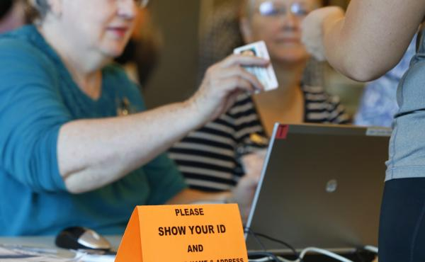 A Utah poll worker checks a voter ID during the 2016 presidential election. Eleven states have strict voter ID laws, while 24 have less stringent laws for an ID to vote. Democrats have begun to lower their resistance to the issue.