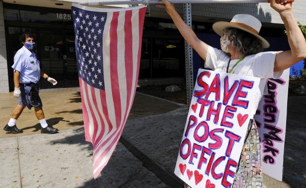 Erica Koesler of Los Angeles demonstrates outside a USPS post office as a postal worker walks by in the background on Saturday. The USPS has warned states coast to coast that it cannot guarantee all ballots cast by mail for the November election will arri