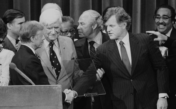 Months after his challenge to the incumbent President Carter had failed, Sen. Edward Kennedy (D-Mass.) makes a belated gesture of unity in the closing moments of the 1980 National Convention.