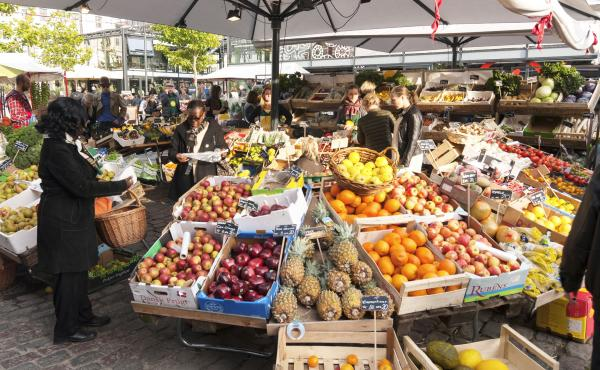 Copenhagen, Denmark - October 11, 2014: fruits and vegetables stalls at market in Copenhagen. Customers are choosing goods for themselves. These stalls is located between market halls where one can find over 60 stands with everything from fresh fish and m