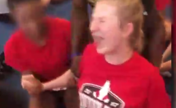 A cheerleader cries out in pain as she is pushed down into a split. Her high school coach was fired on Friday.