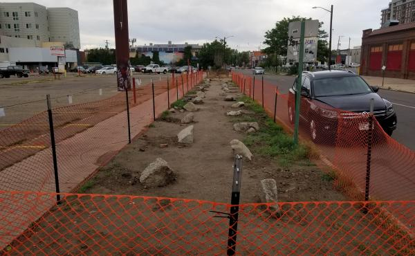 Plastic fencing and landscaping boulders replaced homeless campsites on this block in downtown Denver. Advocates for the homeless fear that displacing encampments risks spreading the coronavirus throughout the homeless community.