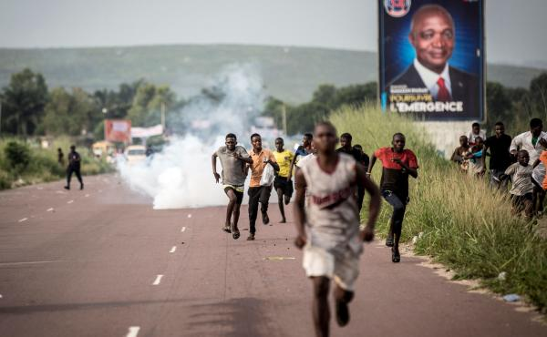 Supporters of opposition leader Martin Fayulu flee a plume of teargas fired by police Wednesday in the capital, Kinshasa.