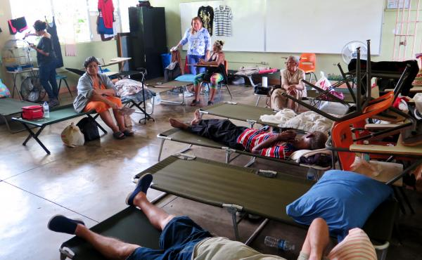 Carmen Rivera, at left in the orange dress, sits on a cot at the Cataño shelter. She suffers from severe asthma and knee pain and has had to be rushed by ambulance to the hospital for asthma treatment twice since the hurricane. She says she feels forgott