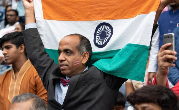 A man holds up an Indian flag during a rally with President Trump and Prime Minister Modi in Houston in September 2019. Trump and Modi have spoken of their friendship, but most Indian Americans say U.S.-India ties are low on their political priorities.