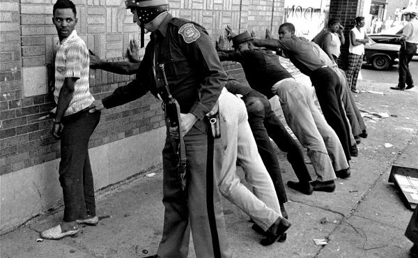 In this photo from July 24, 1967, a police officer searches a youth on Detroit's 12th Street.