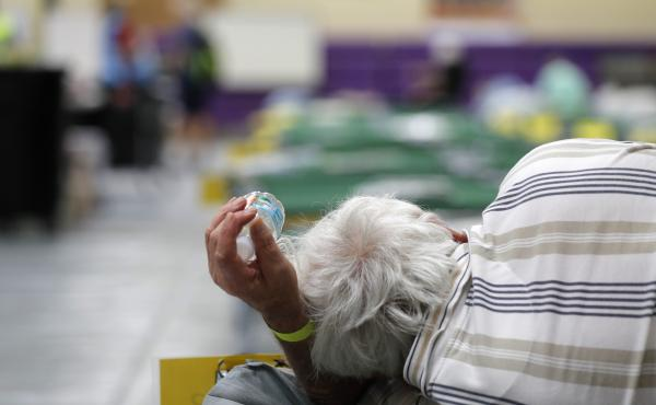 An evacuee lies on a cot at an evacuation shelter for people with disabilities in Stuart, Fla., in preparation for Hurricane Dorian on Sept. 1, 2019. Now, with the pandemic raging, officials across the South are trying to adjust their evacuation and shelt