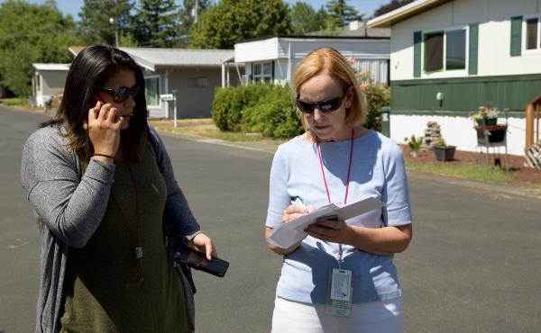 Mary Horman (left), a registered nurse for Clackamas County, and Liz Baca, a disease intervention specialist for the county, search for the right address in an Oregon neighborhood. Part of their job is to get information to people who may have a serious,