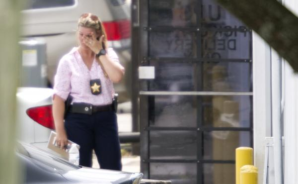 A law enforcement official wipes her eyes at the entrance to the scene of a workplace shooting near Orlando, Fla., on Monday. Authorities say the suspect was fired from the company in April and then returned and shot and killed five people before killing