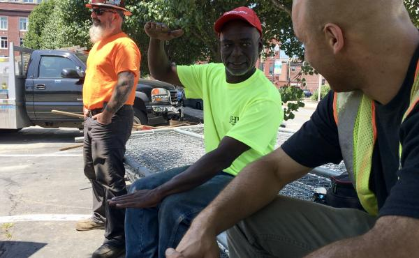 Calvin Brandford (center) is a certified minority contractor who has run an excavation business north of Boston for almost 30 years. Brandford said getting state-funded work as a subcontractor is very hard and often comes with a serious drawback: not gett