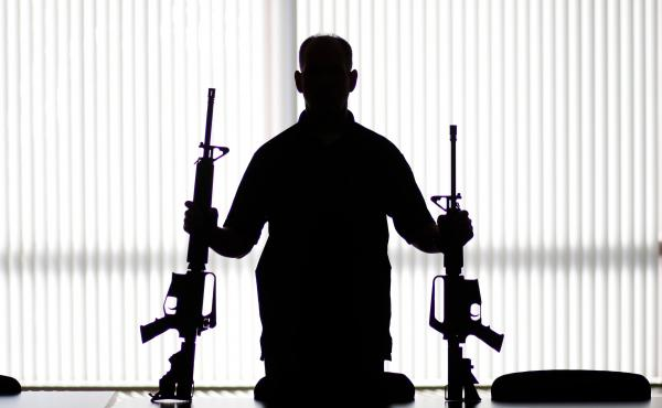 """An ATF agent poses with homemade rifles, or """"ghost guns,"""" at an agency field office in Glendale, Calif. There's a growing industry of companies that sell gun kits, instructions and do-it-yourself components online to help people build their own guns."""