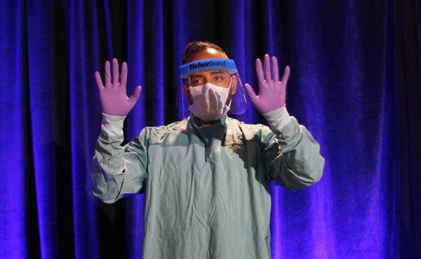 One of the most commonly heard Ebola acronyms is PPE, for personal protective equipment. Above, the proper way to don PPE is demonstrated at a CDC presentation. If you're not sure what CDC stands for, see the list of acronyms below.