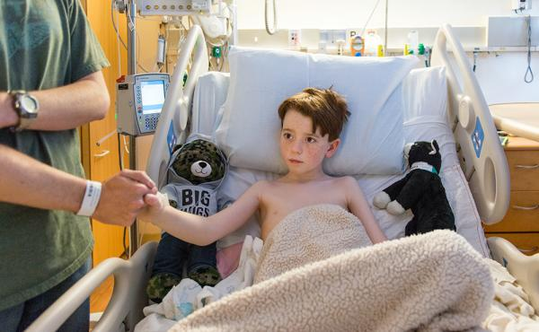 Ten-year-old Matthew Husby gets some low-tech comfort from his father after surgery at Lucile Packard Children's Hospital Stanford in Palo Alto, Calif.