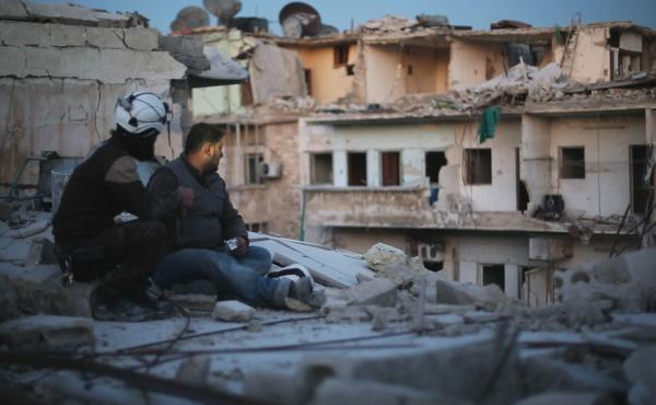 """Two members of """"The White Helmets"""" pause to take stock in the documentary Last Men in Aleppo."""