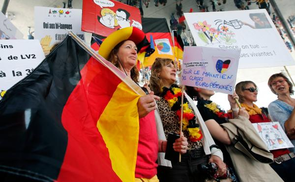 Striking French teachers hold a German flag as they take part in a nationwide protest against new measures aimed at revamping the country's school system, in Marseille, France, on May 19. France's 840,000 teachers are largely opposed to the reform, their