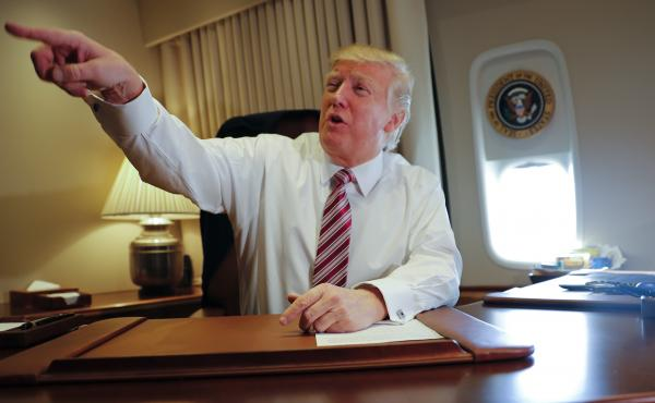 President Trump points toward members of the media while seated at his desk on Air Force One Thursday.