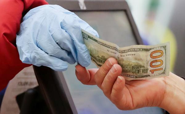 A woman wearing gloves pays for her purchase at a supermarket in Los Angeles. Bank regulators are urging consumers not to hoard cash, after reports of large withdrawals by some customers worried about the coronavirus.