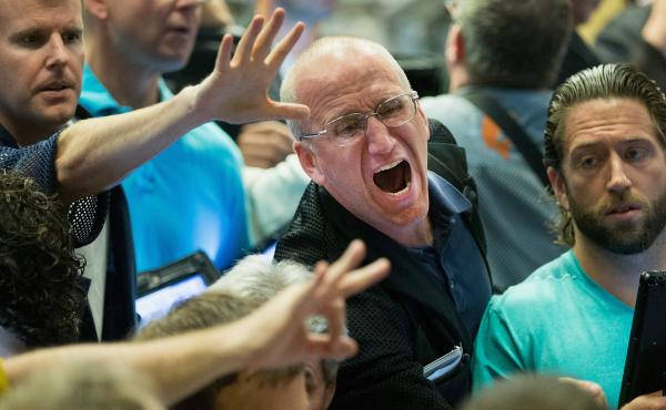 Traders signal offers Monday in the Standard & Poor's 500 stock index options pit at the Chicago Board Options Exchange. Major market indexes tumbled around the world amid worries about China's slowing economy.