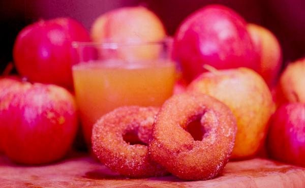 A cold, crisp glass of apple cider helps wash down those deliciously oily donuts, still hot from the fryer.
