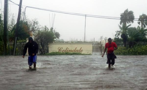 Residents wade through a street flooded with water brought on by Hurricane Dorian in Freeport, Bahamas, on Tuesday. The storm spent most of Monday and into the morning Tuesday essentially stalled out over the Bahamas, relentlessly pounding the islands wit