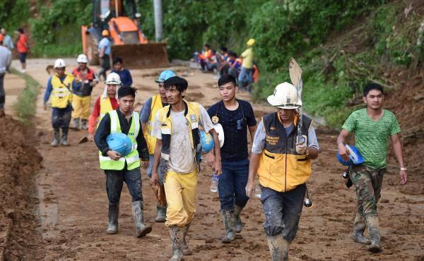 Volunteer rescuers head home after working to dig out victims of a landslide triggered by heavy rains from Typhoon Mangkhut in the Philippine's Benguet province on Monday.