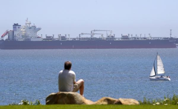 The oil tanker Pegasus Voyager sits off the coast as a man sits and watches in a park in Long Beach, Calif., on April 22. Many vessels are parked between Long Beach and the San Francisco Bay Area with nowhere to go due to lack of demand and nowhere to sto