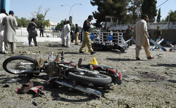 Pakistani security officials inspect the site of an explosion in Quetta on Friday. All told, dozens of people were killed Friday in several cities across Pakistan.