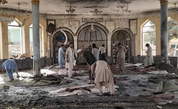 People sift through the damage inside of a mosque following a bombing in Kunduz province northern Afghanistan on Friday.