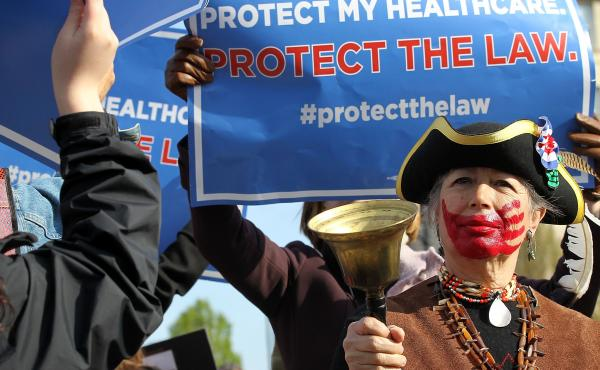 A Tea Party supporter rings a bell in protest of the health care law in front of the U.S. Supreme Court, as Obamacare supporters shout behind her.