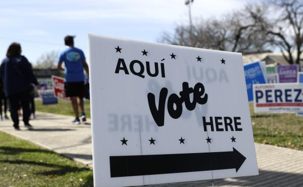 Pedestrians pass signs near a polling site in San Antonio in February.