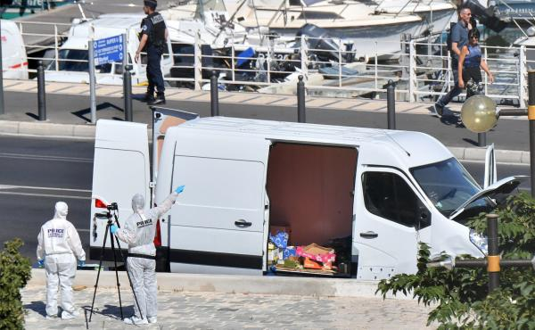 French forensic police officers gesture to pedestrians as they take images while searching a vehicle following a car crash in the southern Mediterranean city of Marseille on Monday.
