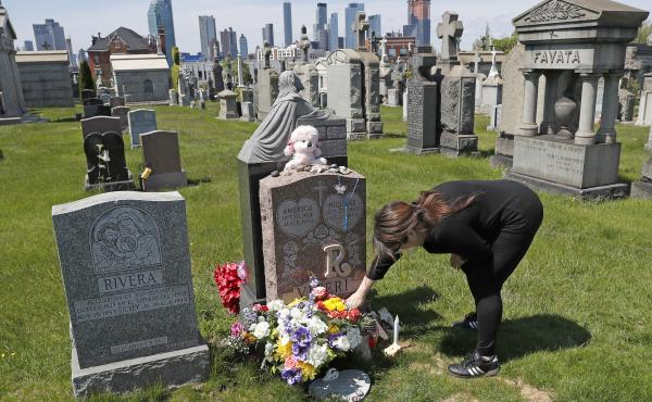 Sharon Rivera adjusts flowers at daughter Victoria's grave at Calvary Cemetery in New York City in 2020. Her daughter, 21, died of a drug overdose in 2019. According to new CDC data, drug overdose deaths soared to more than 93,000 last year.