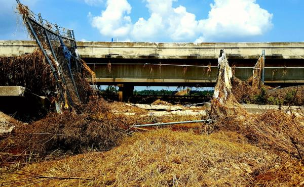 Floodwaters from Hurricane Harvey ripped apart fences and flooded Interstate 10 east of Houston last year. The San Jacinto Waste Pits Superfund site is on the other side of the road.