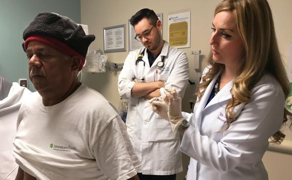 Francisco Hidalgo prepares to receive a trigger point injection from Dr. Alexis LaPietra (right) at St. Joseph's University Medical Center in Paterson, N.J., while Dr. Tyler Manis observes. An alternative to opioids, the trigger point injection involves d