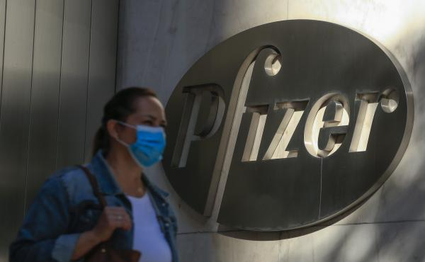 A woman wears a mask as she walks by Pfizer's world headquarters in New York last month.