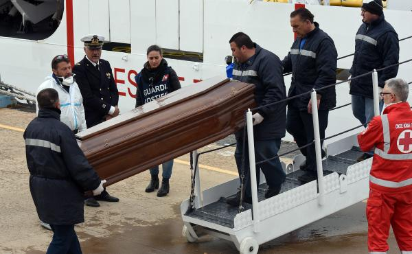 """Men carry a coffin during the arrival of migrants and refugees in the port of Messina following a rescue operation at sea by the Italian Coast Guard ship """"Diciotti"""" on March 17 in Sicily. After several quiet weeks, March saw a pickup in the flow of migran"""