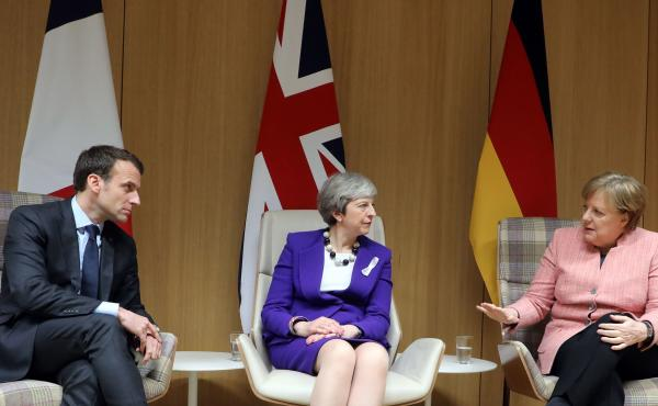 British Prime Minister Theresa May, center, with German Chancellor Angela Merkel, right, and French President Emmanuel Macron during a news conference following a meeting on the sidelines of the European Union leaders summit in Brussels, on Thursday.