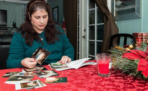 Rosemary Navarro, 40, looks through old childhood photographs at her home in La Habra, Calif. Her mother, Rosa Maria Navarro, passed away in 2009 from Alzheimer's.