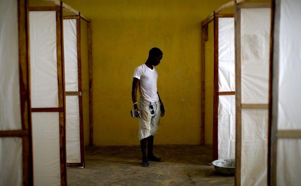 In November 2014, a worker stands by dividers to separate patients in an Ebola treatment facility under construction in the Port Loko district of Sierra Leone.