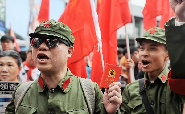 Protesters dressed as Chinese Red Guards chant during a May demonstration in Tsim Sha Tsui, Hong Kong. People from Hong Kong staged a satirical rally to urge Chinese tourists to stay in mainland China. Competition for housing, grades and jobs between the