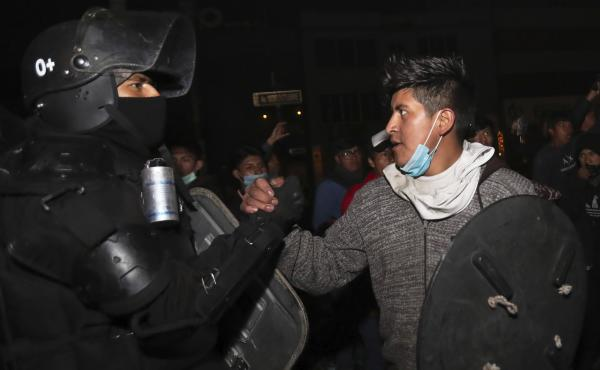 A protester shakes hands with a security officer in Quito, Ecuador, on Sunday as they celebrate the government's announcement that it has cancelled an austerity package. The package had triggered violent protests that paralyzed the economy and left seven