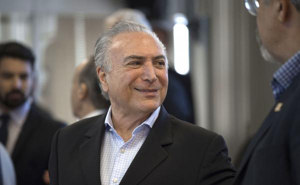 Brazilian President Michel Temer flashes a smile during a meeting in Rio de Janeiro on Sunday. The embattled leader has been one of the subjects of a vast, yearslong corruption probe that has snared many of the country's most powerful politicians and busi