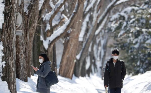 Passersby wearing protective masks walk on a snow-covered street in Sapporo, Hokkaido, Japan, in late February during the first wave of the novel coronavirus. Now, officials have declared a new state of emergency as cases in Hokkaido spike.