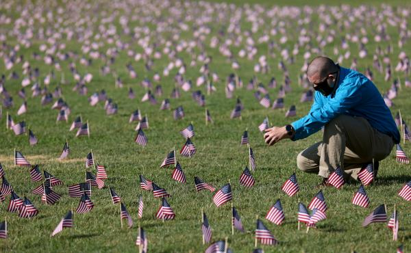 The U.S. hit a tragic milestone Tuesday, recording more than 200,000 coronavirus deaths. Here, Chris Duncan, whose 75-year-old mother, Constance, died from COVID-19 on her birthday, visits a COVID Memorial Project installation of 20,000 U.S. flags on the