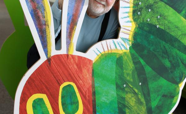 Eric Carle with a cutout of his famously hungry caterpillar at the Eric Carle Museum of Picture Book Art in Amherst, Mass.
