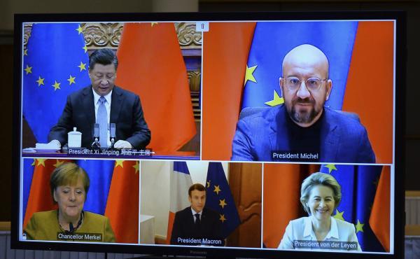 A screen displays Chinese President Xi Jinping (top left), European Council President Charles Michel (top right), European Commission President Ursula von der Leyen (bottom right), French President Emmanuel Macron and German Chancellor Angela Merkel durin